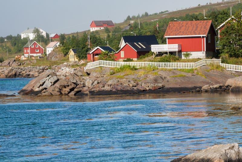 Rote und gelbe hölzerne Fischenkabinen in Norwegen lizenzfreie stockbilder