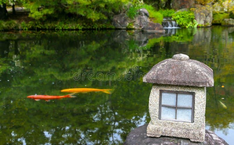 Rote und gelbe Karpfenfische in einem Zen stauen in Japan mit Laterne stockfotografie