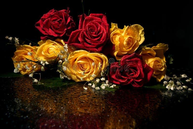 Rote und gelbe Rosen auf einem Spiegel schwärzen Oberfläche lizenzfreies stockfoto