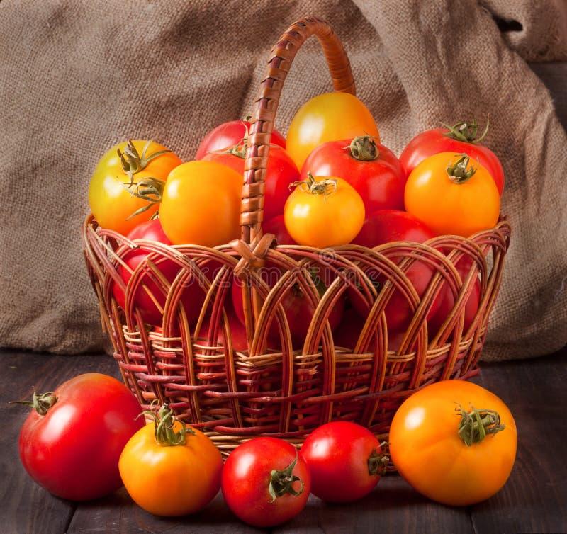Rote und gelbe Tomaten in einem Weidenkorb auf Holztisch stockfotografie