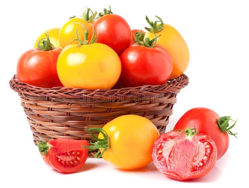 Rote und gelbe Tomaten in einem Weidenkorb lokalisiert auf weißem Hintergrund lizenzfreies stockfoto