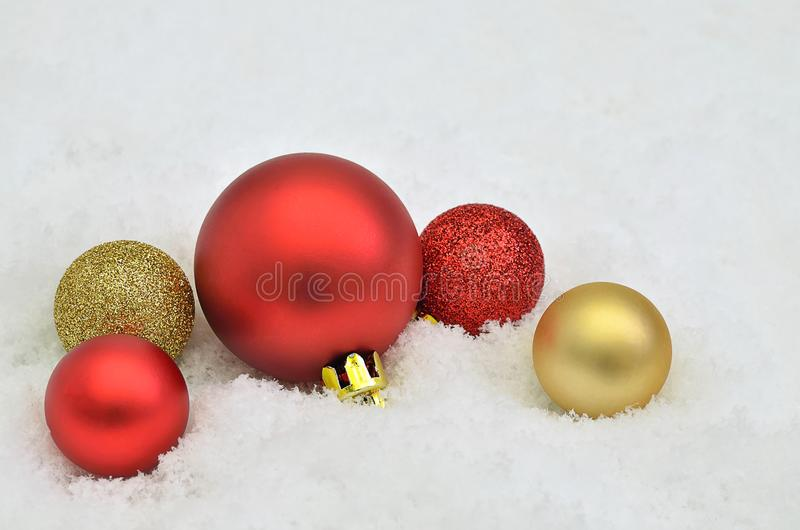 Rote und goldene Christbaumkugeln auf Schneehintergrund stockbild