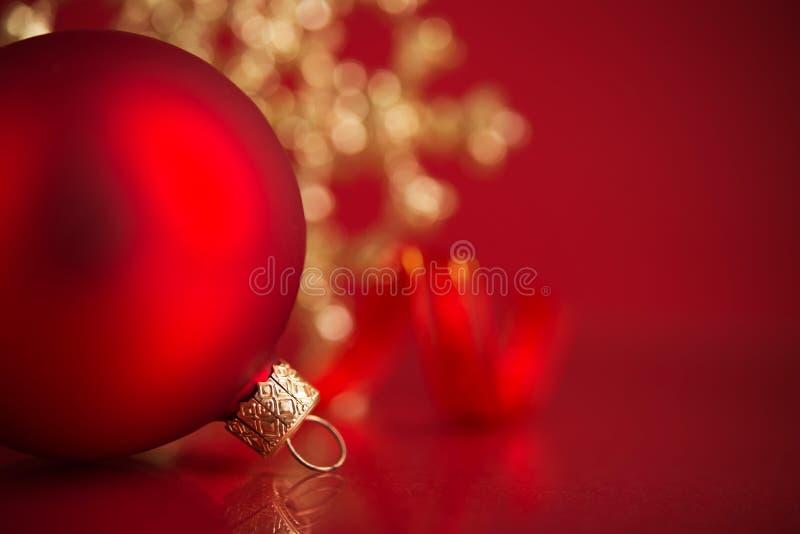 Rote und goldene Weihnachtsverzierungen auf rotem Hintergrund mit Kopienraum lizenzfreie stockbilder