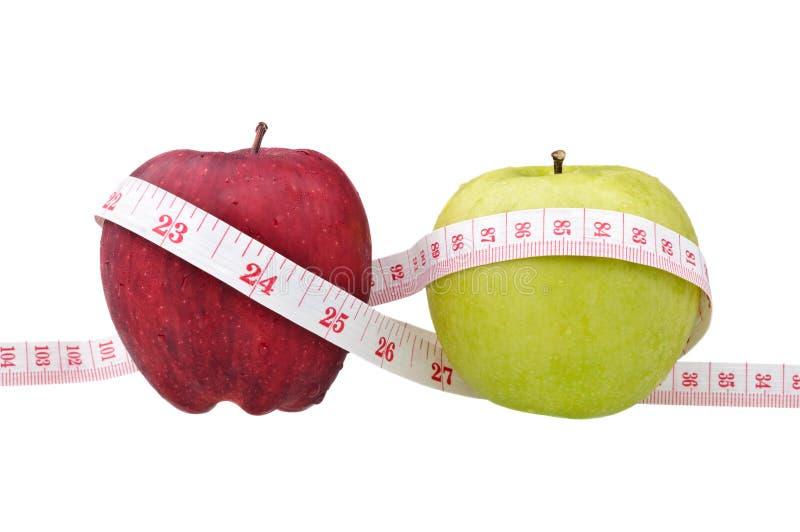 Rote und grüne Äpfel mit Maßband stockbild