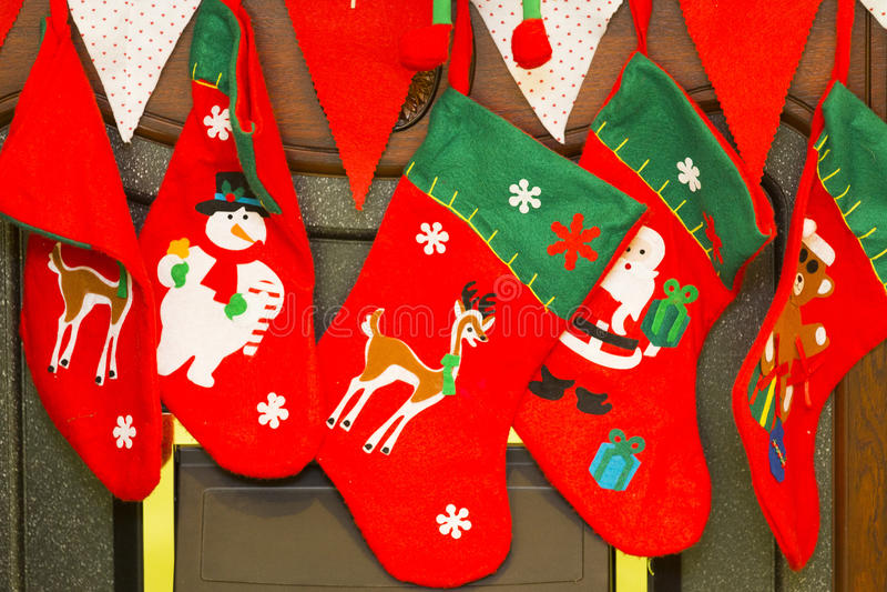 Rote und grüne Weihnachtsstrümpfe mit Schneemann, Sankt und Rotwild stockbilder