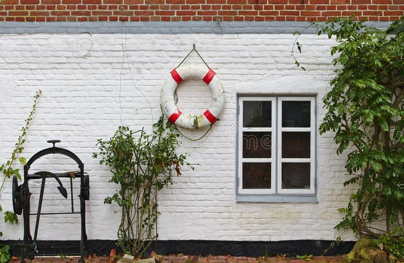 Rote und rehabilitierte Backsteinmauer mit Fenster, grüne Büsche, rote und weiße Lebenboje und historische Ankerwinde lizenzfreies stockfoto