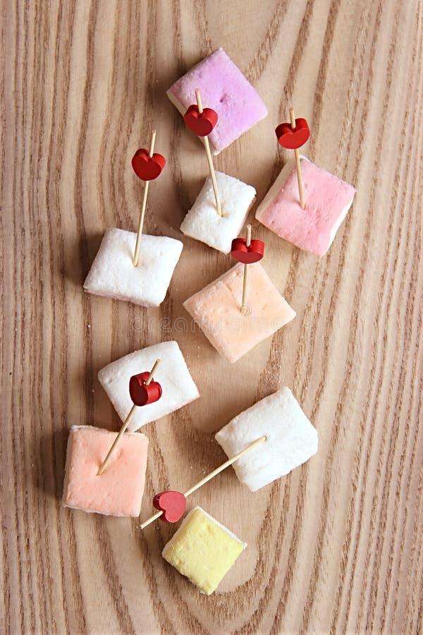 Rote und rosa hölzerne Aufsteckspindeln und farbige Eibische für Lebensmittel mit einem Herzen Nachtisch auf hölzernem Hintergrun lizenzfreies stockbild