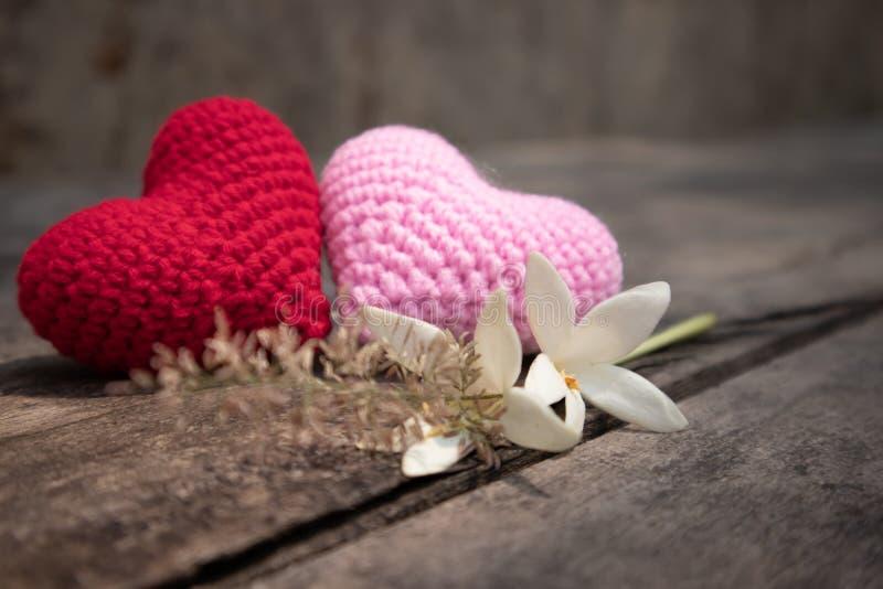 Rote und rosa strickende Herzen mit Millingonia auf der hölzernen rauen Tabelle Hintergrund der Felsenwand Sun-Lichtglanz auf dem stockfotografie