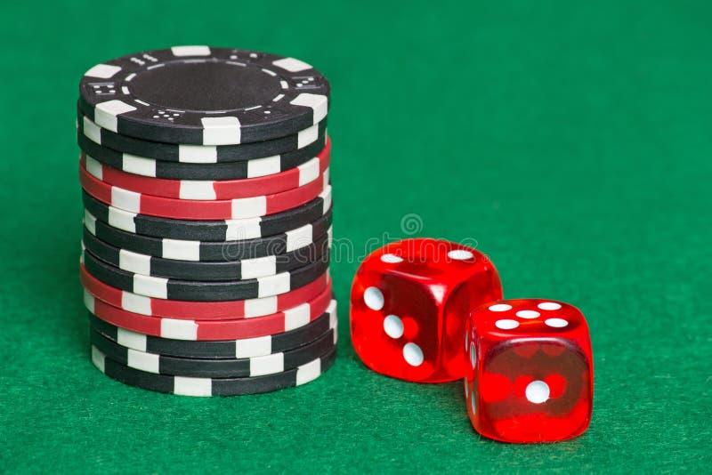 Rote und schwarze Pokerchips und Würfel auf einem grünen Kasinofilz lizenzfreie stockfotos