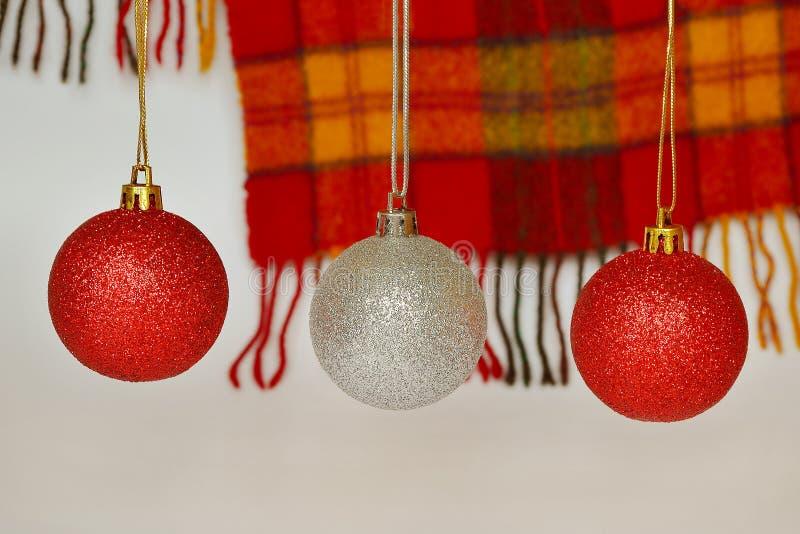 Rote und silberne Weihnachtsbälle gegen einen woolen roten und gelben karierten Schal mit einer Franse Konzept von Feiertagen, vo stockfotos
