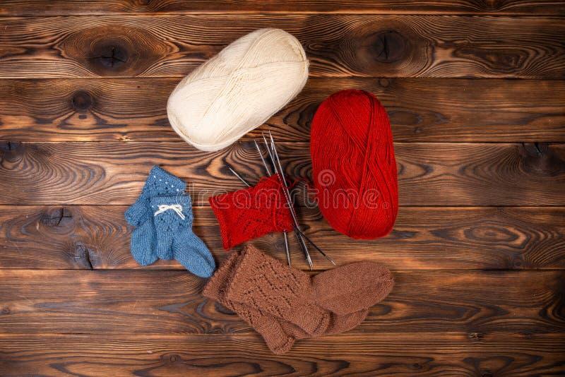 Rote und weiße farbige Bälle des Fadens, der Stricknadeln und der gestrickten Socken auf einem hölzernen Hintergrund stockbilder