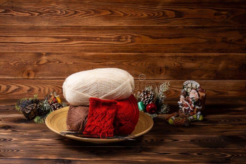 Rote und weiße farbige Bälle des Fadens, der Stricknadeln und der Weihnachtsspielwaren auf hölzernem Hintergrund lizenzfreie stockfotos