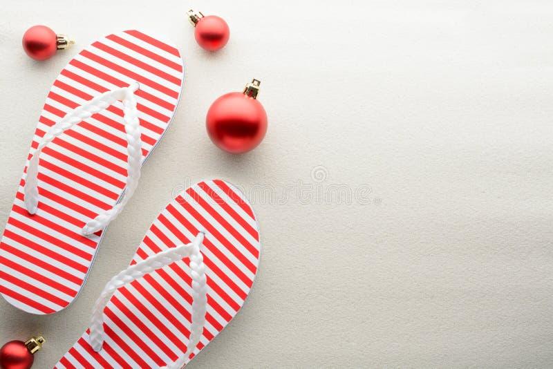 Rote und weiße Flipflops und Weihnachtsverzierungen stockfotografie