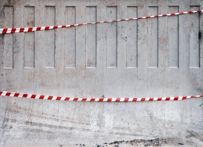 Rote und weiße gestreifte Bänder auf Betonschranke lizenzfreie stockbilder