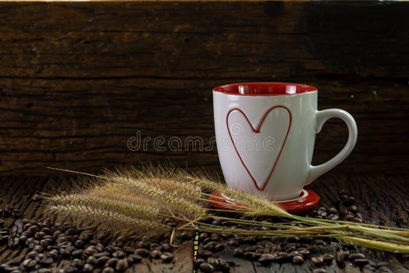Rote und weiße Kaffeetasse mit Herzformmuster, Blumen des trockenen Grases und Kaffeebohnen auf hölzerner Tabelle stockbild