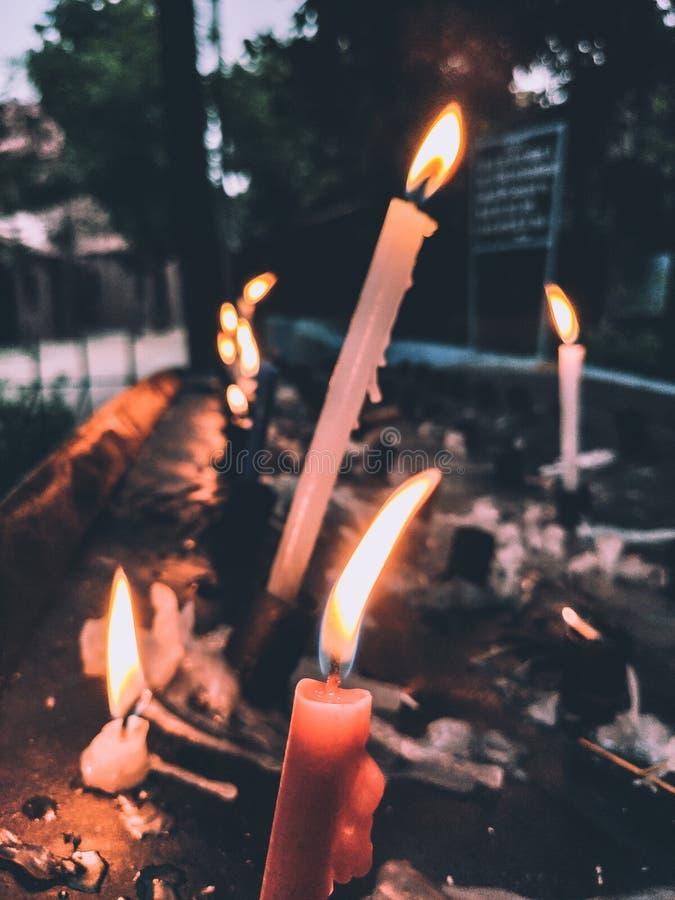 Rote und weiße Kerzen, die in die Dunkelheit glühen stockfoto
