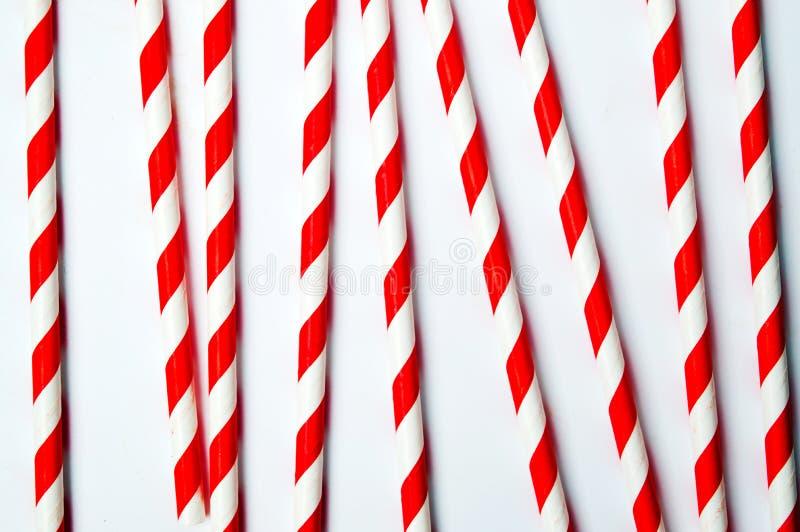 Rote und weiße Strohe auf weißem Hintergrund stockfotografie