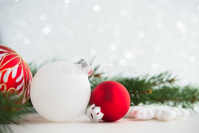 Rote und weiße Weihnachtsverzierungen auf Funkelnfeiertagshintergrund Frohe Weihnacht-Karte stockbilder