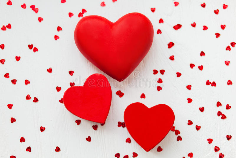 Rote Valentinsgrußherzen auf einem weißen hölzernen Hintergrund lizenzfreie stockbilder