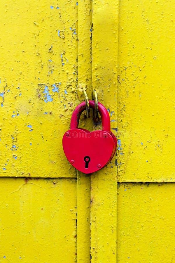 Rote Verriegelung auf einer rostigen gelben Tür stockbilder