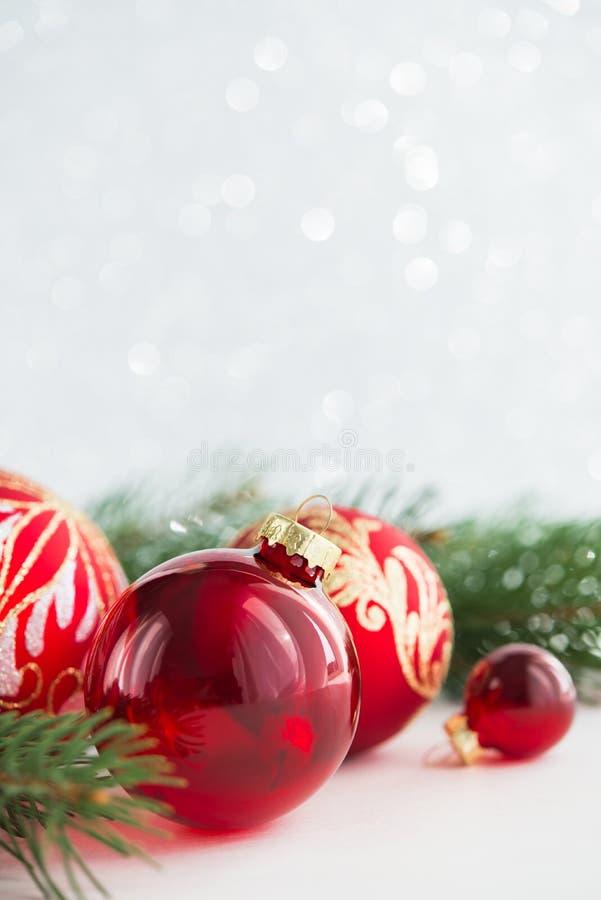 Rote Verzierungen und Weihnachtsbaum auf Funkelnfeiertagshintergrund Frohe Weihnacht-Karte lizenzfreie stockfotos