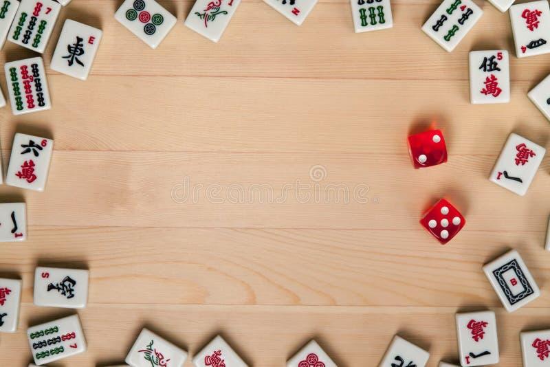 Rote Würfel- und Knochenfliesen für mahjong auf einem hellbraunen hölzernen Hintergrund stockbild
