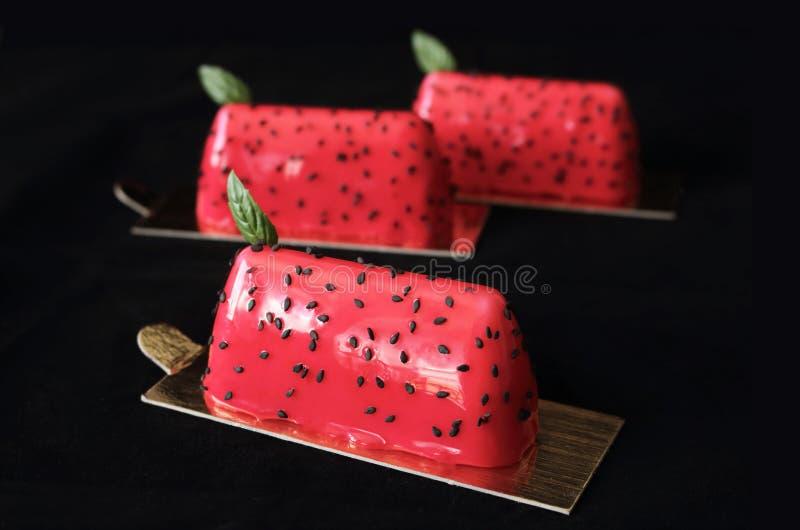 Rote Wassermelone glasierte glänzende Nachtische mit schwarzen Samen des indischen Sesams und den Basilikumblättern, die auf schw stockfoto