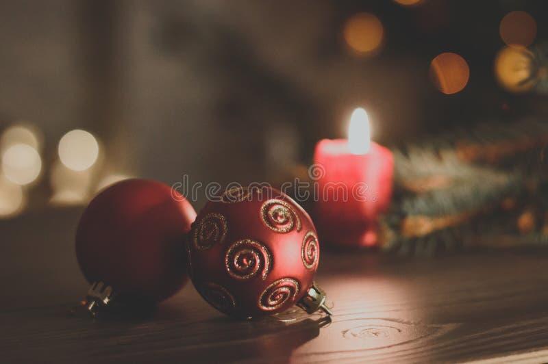 Rote Weihnachtsbälle auf dem Hintergrund einer brennenden Kerze und der FI stockfotografie