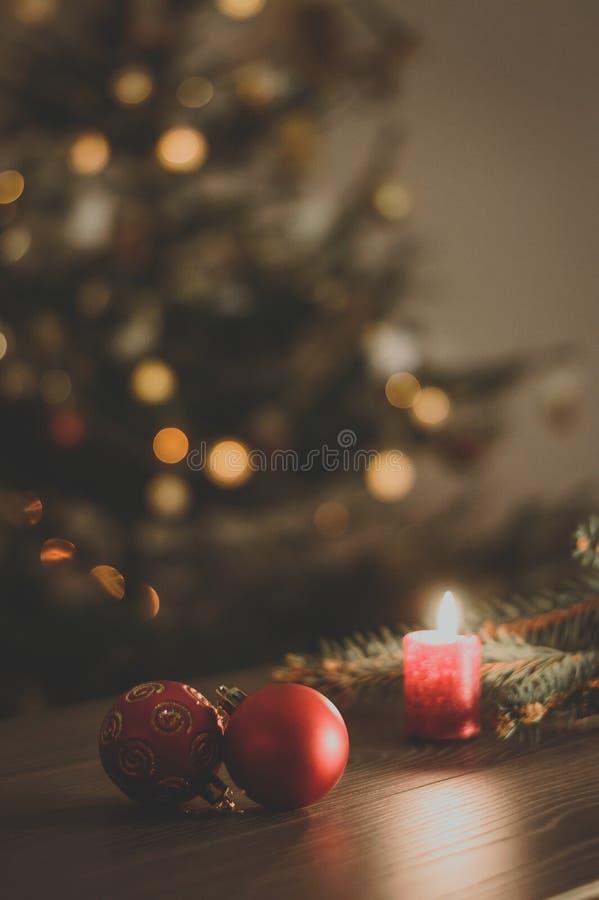 Rote Weihnachtsbälle auf dem Hintergrund einer brennenden Kerze und des Ch lizenzfreies stockbild