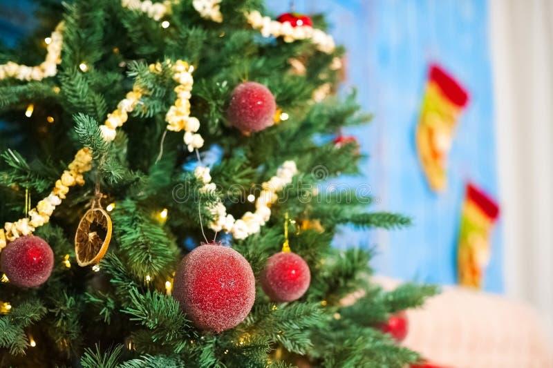 Rote Weihnachtsbälle auf einem Weihnachtsbaum auf einem Hintergrund von blauen alten Türen im neues Jahr ` s Raum verziert Girlan stockfoto