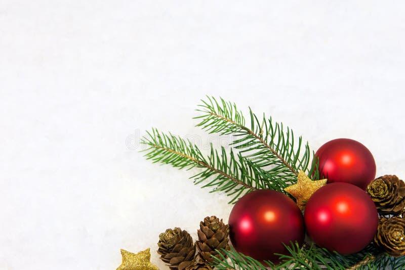 Rote Weihnachtsbälle auf schneebedecktem Hintergrund lizenzfreie stockfotografie