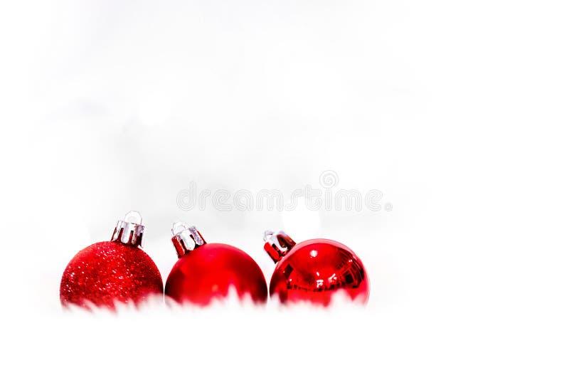Rote Weihnachtsbälle auf weißem Schnee auf hellem Hintergrund, neuem Jahr und Weihnachtshintergründen stockfotografie