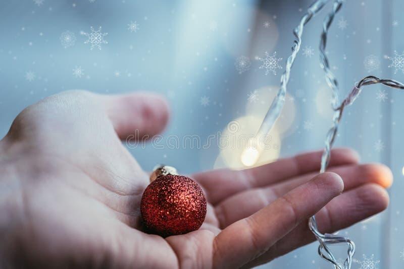 Rote Weihnachtsbälle mit Dekoration auf glänzendem Hintergrund, außerhalb in der Hand halten lizenzfreie stockfotografie