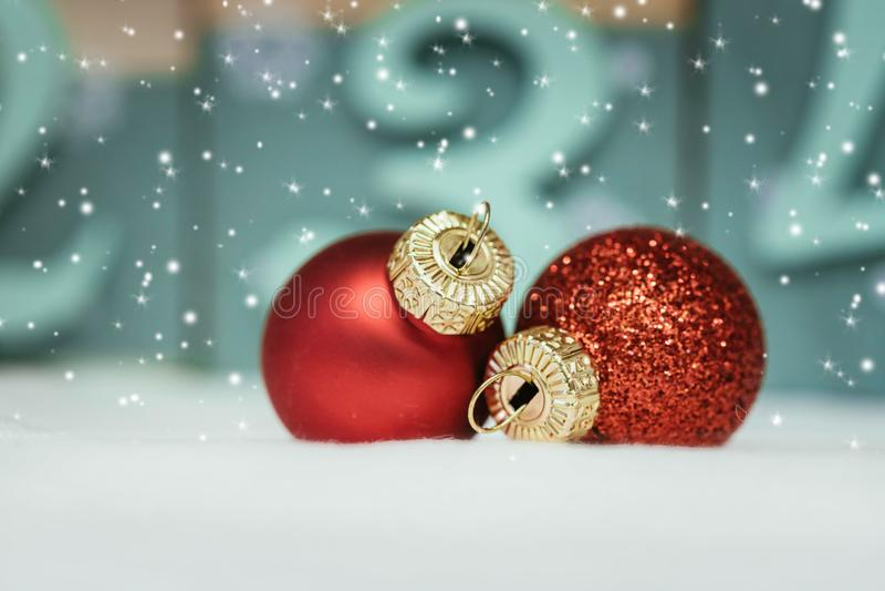 Rote Weihnachtsbälle mit Dekoration auf glänzendem Hintergrund mit Schneeflocken lizenzfreies stockfoto