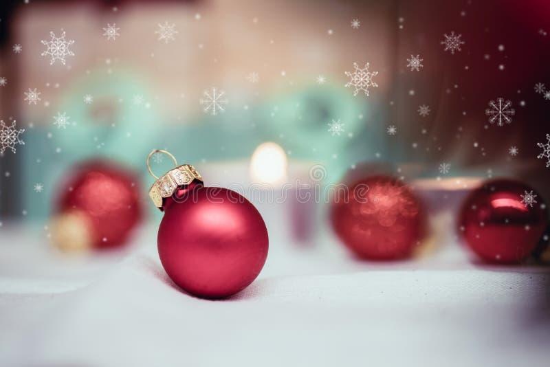 Rote Weihnachtsbälle mit Dekoration auf glänzendem Hintergrund mit Schneeflocken stockbilder