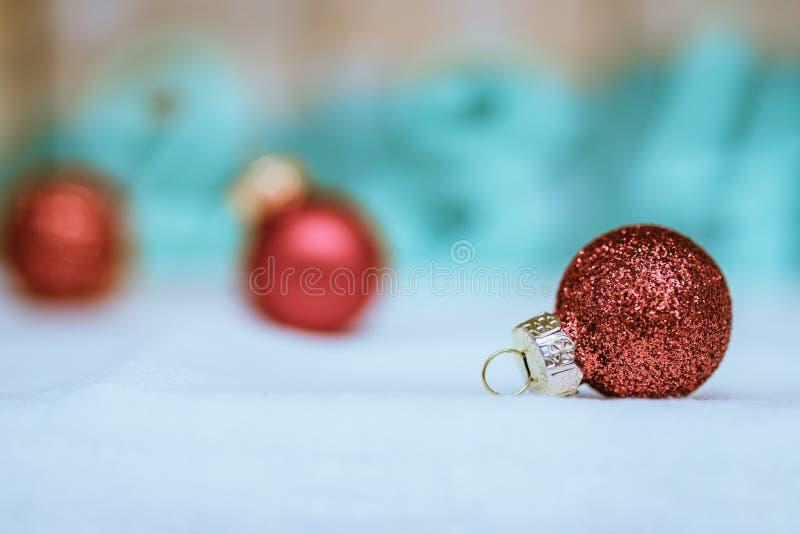 Rote Weihnachtsb?lle mit Dekoration auf gl?nzendem Hintergrund lizenzfreie stockbilder