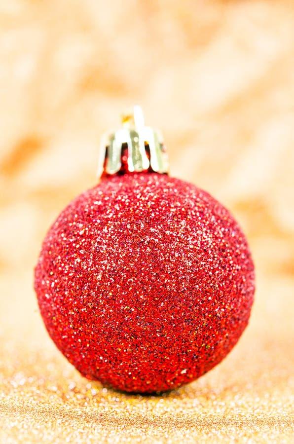 Rote Weihnachtsbaumdekorationen auf goldenen Lichtern stockbild