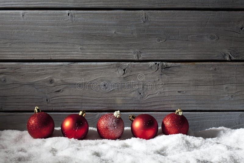 Rote Weihnachtsbereiche auf Stapel des Schnees gegen hölzerne Wand lizenzfreie stockfotografie