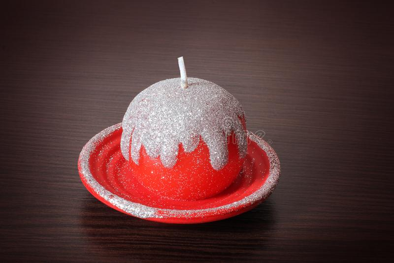 Rote Weihnachtskerze auf einem hölzernen Hintergrund lizenzfreies stockbild