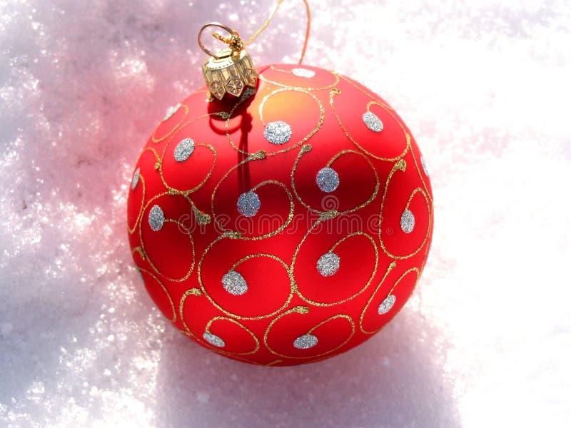 Rote Weihnachtskugel auf Schnee lizenzfreie stockfotos