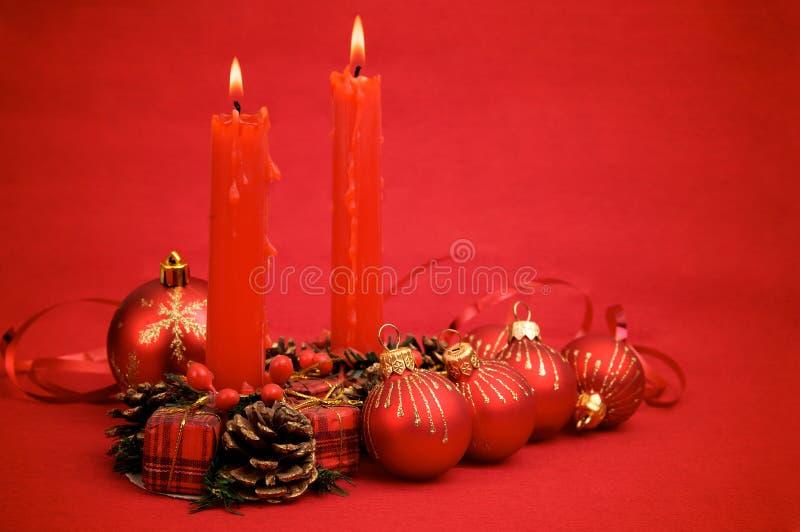 Rote Weihnachtskugeln und -kerzen stockbild
