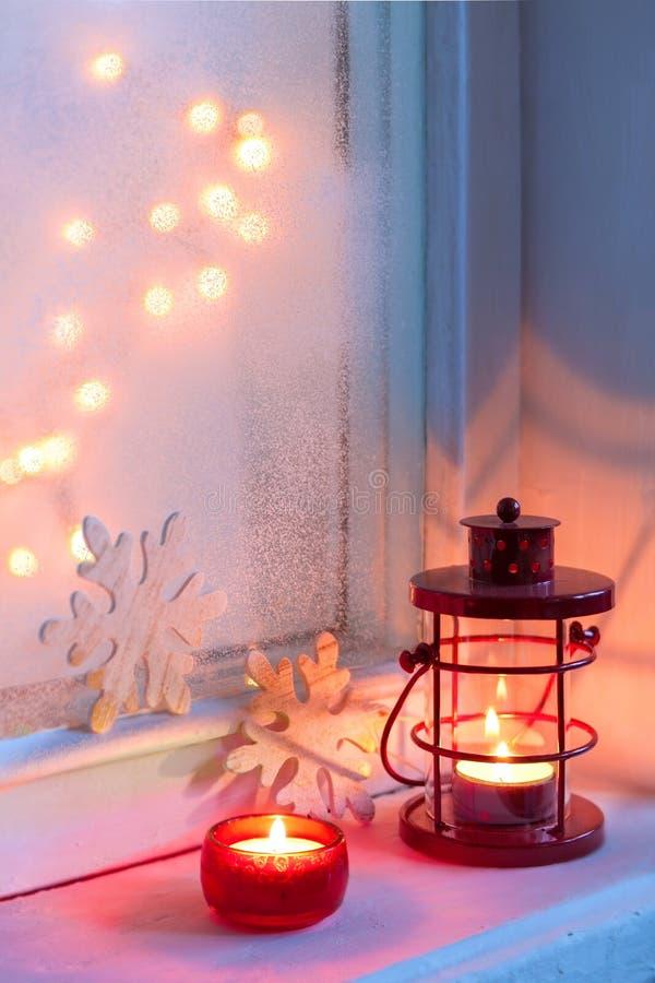 Rote Weihnachtslaterne und -kerze in der Dämmerung auf altem Fensterbrett stockfotos