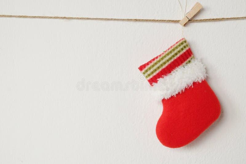 Rote Weihnachtssocke, die am weißen Wandhintergrund hängt stockfotografie