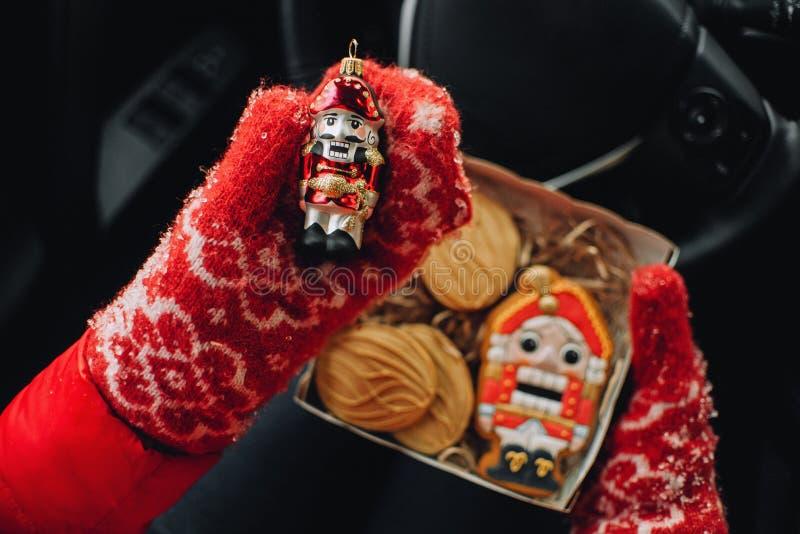 Rote Weihnachtsspielwaren und -plätzchen in den Händen lizenzfreie stockfotografie