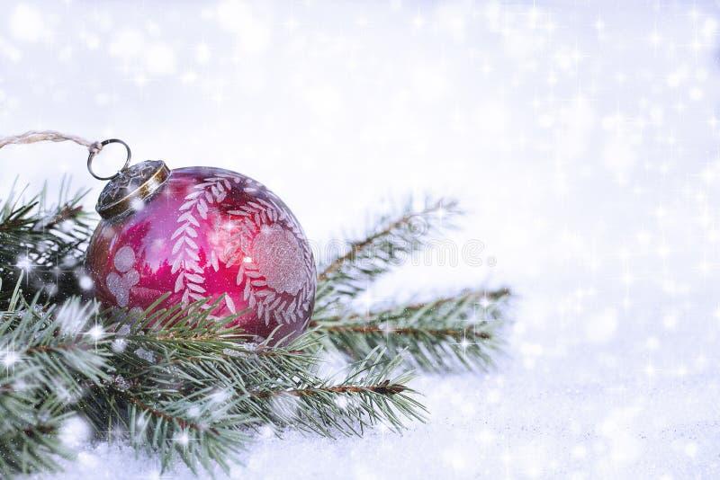 Rote Weihnachtsverzierung auf Kiefern-Niederlassungen und Schnee lizenzfreie stockfotos