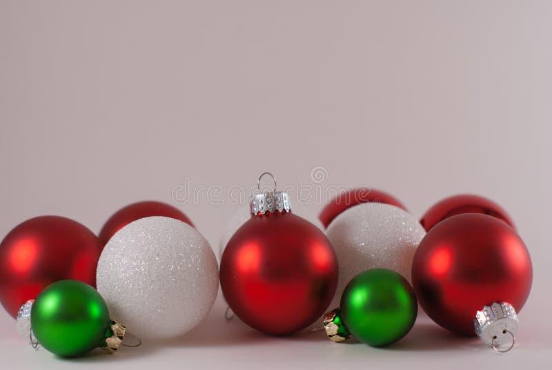 6 rote Weihnachtsverzierungen gemischt mit den weißen und kleinen grünen Verzierungen mit einem weißen Hintergrund lizenzfreies stockfoto