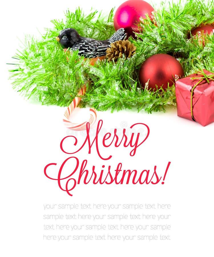 Rote Weihnachtsverzierungen und Weihnachtsbaum auf weißem Hintergrund Frohe Weihnacht-Karte Der Junge gelegt auf den Schnee Thema stockfoto