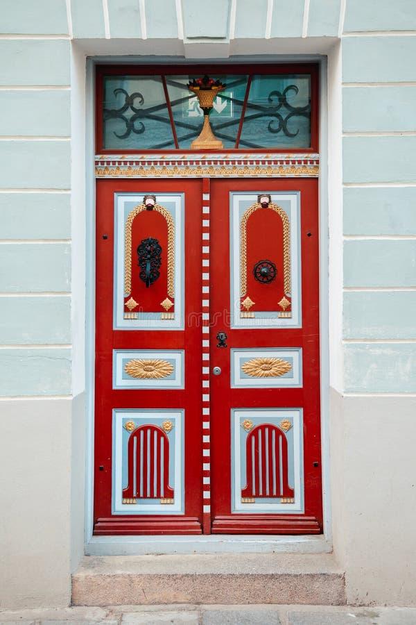 Rote Weinlesetür auf einer Altbaufassade in alter Tallinn-Stadt lizenzfreies stockfoto