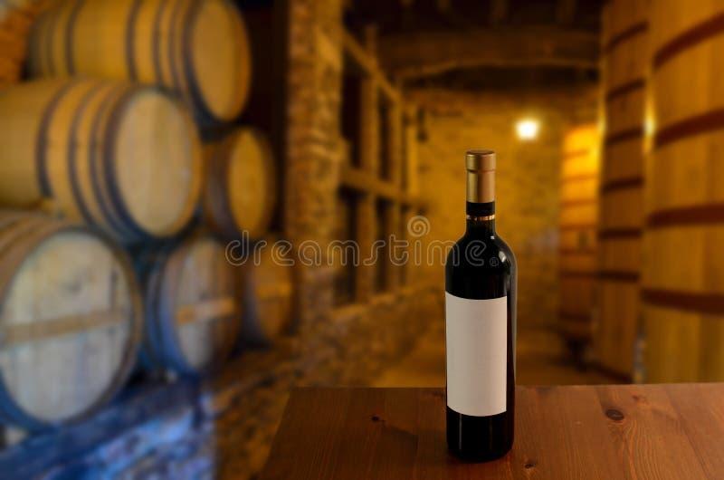 Rote Weinprobe in einem alten Weinkeller mit hölzernen Weinfässern in einer Weinkellerei stockbild