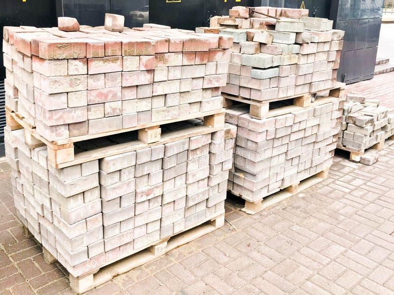 Rote Zementfliese des Pflastersteins für das Legen des Straßenbaus, Pflasterung auf hölzernen Paletten an einer Baustelle lizenzfreies stockfoto